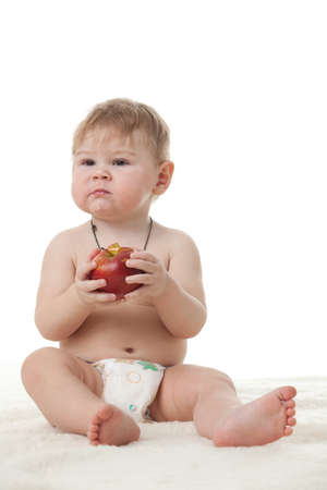 Sweet small baby with a fresh red apple on a white background. Stock Photo - 8806956