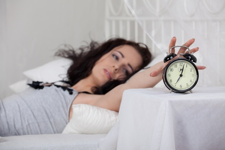 Young sleeping woman and alarm clock in bedroom at home. Stock Photo - 8818407