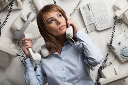 Stressed  young businesswoman with telephones in her hands. photo