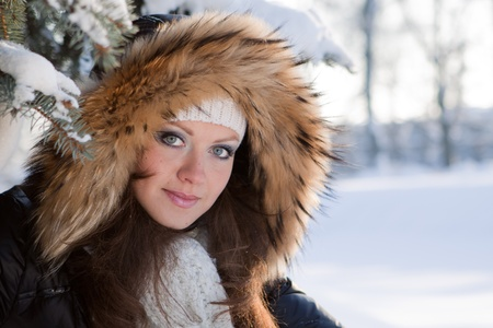 fur hood: The beautiful young woman in winter snow-covered wood. Stock Photo