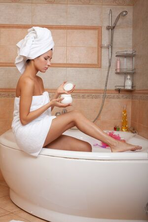 Young woman with cosmetic cream in a bathroom. Concept body care. photo
