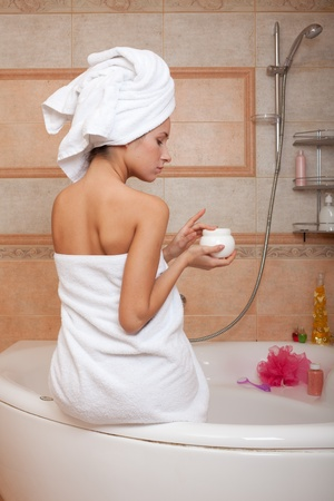 Young woman with cosmetic cream in a bathroom. Concept body care. Stock Photo - 8926142