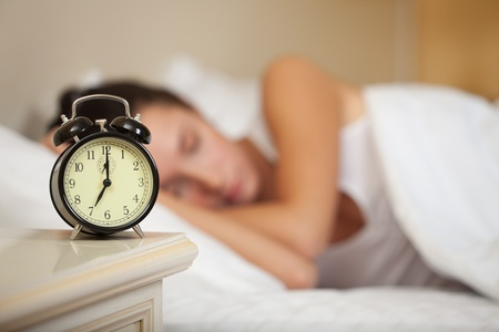 Young sleeping woman and alarm clock in bedroom at home. Stock Photo - 8922807