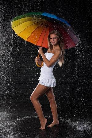 Young pretty woman with multi-coloured umbrella under rain on a black background. Stock Photo - 8923004