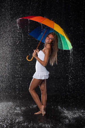 Young pretty woman with multi-coloured umbrella under rain on a black background. Stock Photo - 8923005