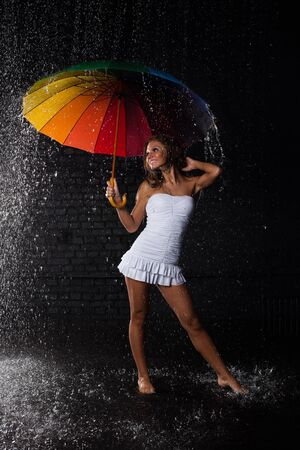 Young pretty woman with multi-coloured umbrella under rain on a black background. Stock Photo - 8922998