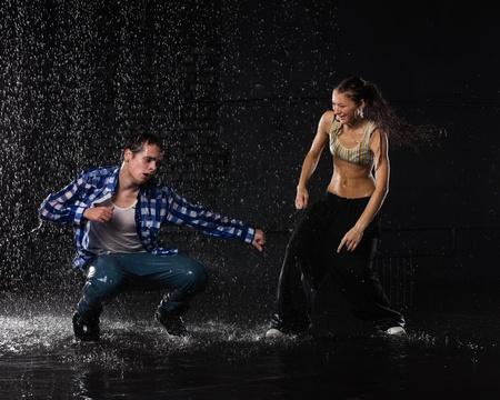 Jong paar dansen in het water onder regen op een zwarte achtergrond. Moderne dansen.