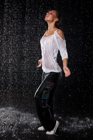 The beautiful girl dancing in water under rain on a black background.  Modern dances. Stock Photo - 8923002
