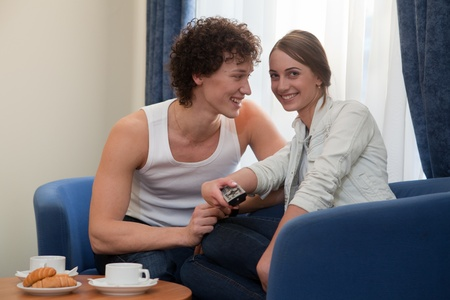 Happy young couple with breakfast sit in the armchair  and watch TV at home. photo