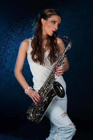 wet jeans: Young beautiful woman with a saxophone stands under rain on a black background.