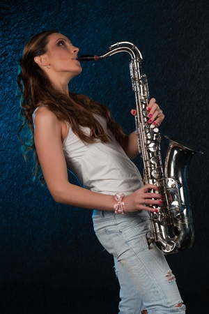 Young beautiful woman with a saxophone stands under rain on a black background. photo