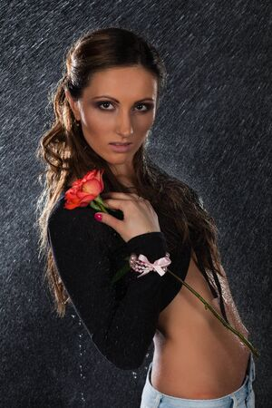 wet jeans: Young beautiful woman with rose stands under rain on a black background.