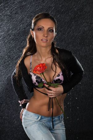 Young beautiful woman with rose stands under rain on a black background. Stock Photo - 8999757