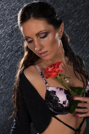 Young beautiful woman with rose stands under rain on a black background. photo