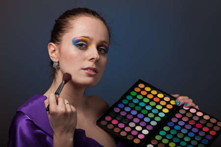 Beautiful young woman with a make-up holds a cosmetic palette. photo