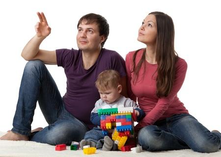 ascending: Familia feliz con dulce beb� construir casa sobre un fondo blanco.  Concepto de construcci�n y compra de la casa. Foto de archivo