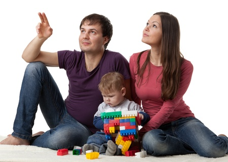 looking upwards: Happy family with sweet baby build house on a white background.  Concept of  building and purchase  of the house.