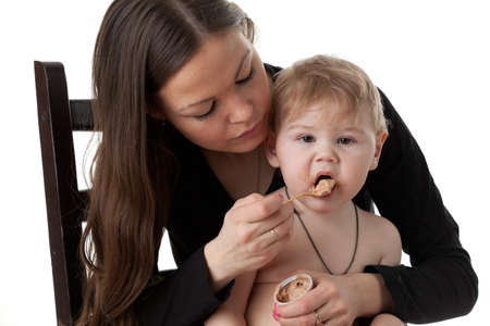 Young mother feeds  her baby on a white background. Happy family. Stock Photo - 8999844