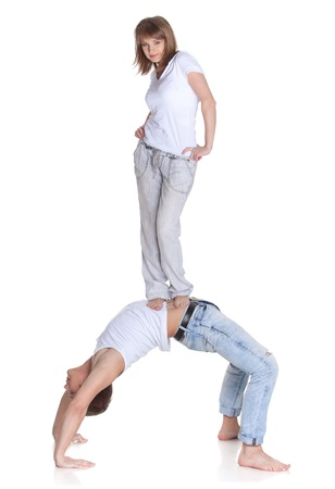 carry out: Young sports people carry out acrobatic tricks on a white background. Concept of teamwork. Stock Photo