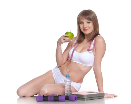 Sporty young woman with scales on a white background. Concept of healthy lifestyle. photo