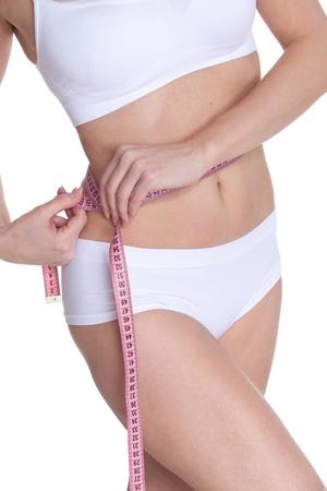 ?tapes: La belle jeune femme mesure un volume de taille sur un fond blanc.  Concept de mode de vie sain. Banque d'images