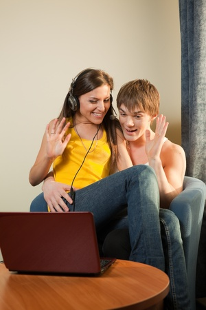 Happy young couple with laptop sit in the armchair  at home. photo