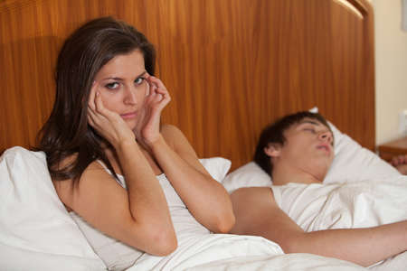 snore: Unhappy woman and her snoring husband in bedroom.