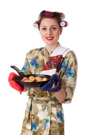 Young beautiful woman with cookies in frying pan on a white background. Housekeeping. photo