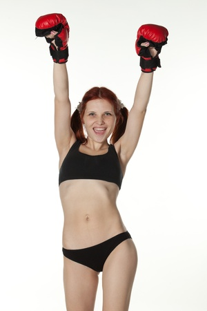 Sporty girl in red fighting gloves on a white background. photo