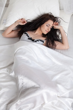 quietude: Portrait of beautiful young woman sleeping in bed at home.
