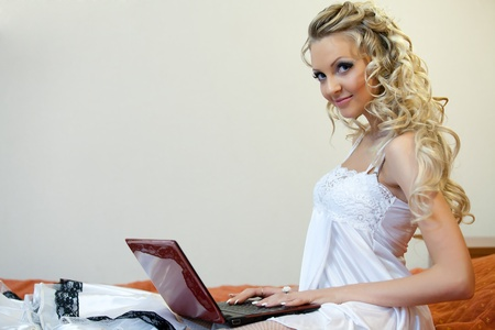 Young woman with wedding dress and laptop sits on the bed at home. Stock Photo - 9162499
