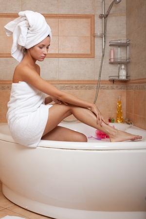 Junge Frau mit kosmetischen Creme im Badezimmer. Konzept Körperpflege.