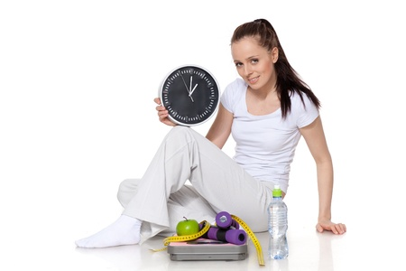 Sporty young woman with clock, scales, dumbbells and apple on a white background.  Time for slimming. Stock Photo - 9198053