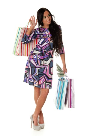Pretty young woman with shopping bags and money on a white background Stock Photo - 9198150