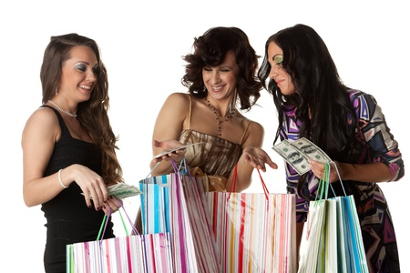Young happy women with money and shopping bags  on a white background. Sale. photo