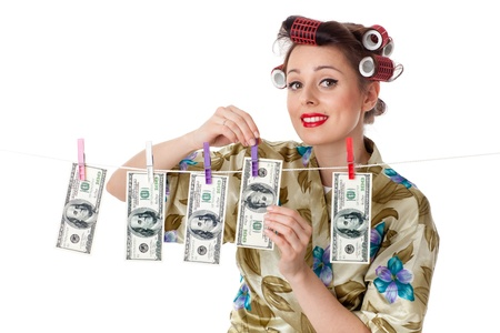 Young housewife is hanging hundred dollar bills on clothesline on a white background.  Money concept. Stock Photo - 9302036