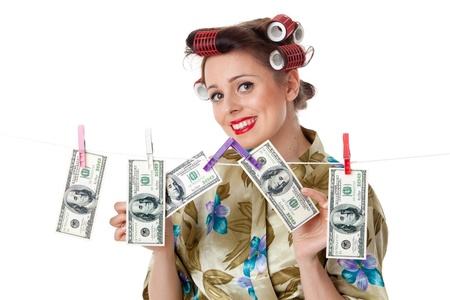 Young housewife is hanging hundred dollar bills on clothesline on a white background.  Money concept. Stock Photo - 9302027