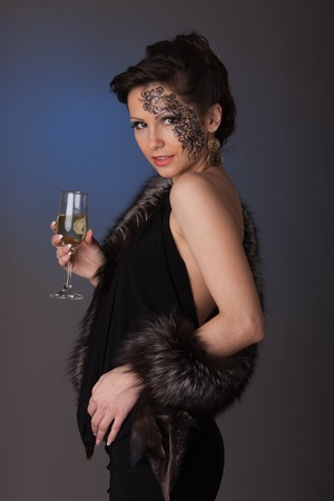Young woman in furs with a glass of champagne. photo