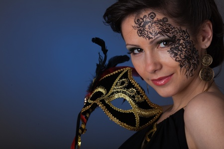 Portrait of a young beautiful woman with mask on a blue background. Stock Photo - 9355926
