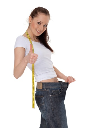 The beautiful young woman in old jeans after losing weight on a white background. Concept of healthy lifestyle. Stock Photo - 9390838