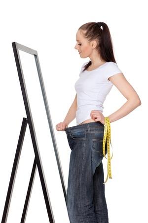 mirar espejo: La joven y bella mujer en viejos jeans despu�s de perder peso sobre un fondo blanco. Concepto de estilo de vida saludable.