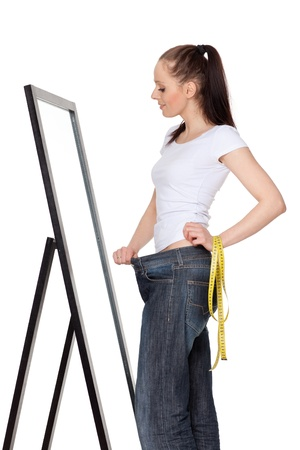 body check: The beautiful young woman in old jeans after losing weight on a white background. Concept of healthy lifestyle.
