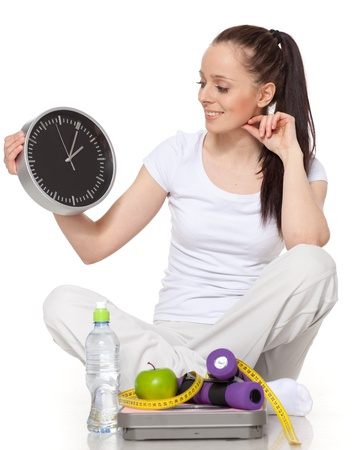 Sporty young woman with clock, scales, dumbbells and apple on a white background.  Time for slimming. photo