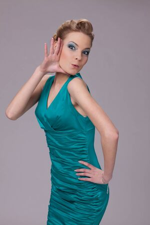 Portrait of the surprised young woman in turquoise dress. photo
