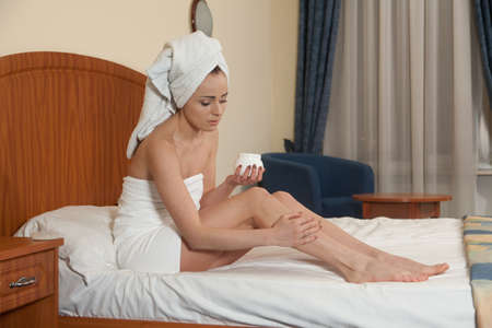 The attractive young woman in towel with cosmetic cream sits on bed at home. Concept of body care. Stock Photo - 9390896