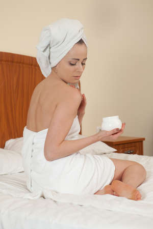 The attractive young woman in towel with cosmetic cream sits on bed at home. Concept of body care. photo
