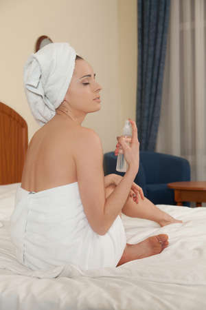 The attractive young woman in towel with cosmetic lotion sits on bed at home. Concept of body care. photo