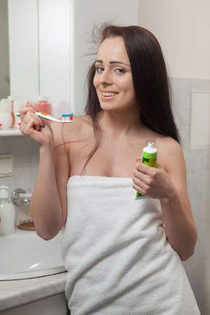 Young happy woman with toothbrush in a bathroom. photo