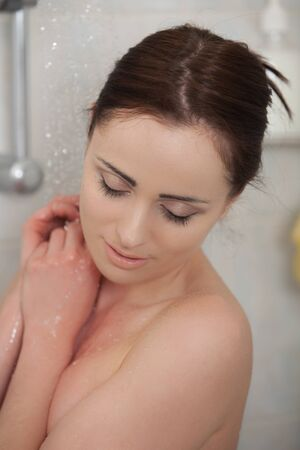 shower cubicle: Portrait of a beautiful young woman in a bathroom. Concept  of body care.
