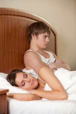 Young couple quarrels in bedroom at home. Family conflict. photo